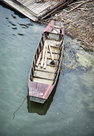 filthiness: Old retro boat in the water, near the shore. View from above.