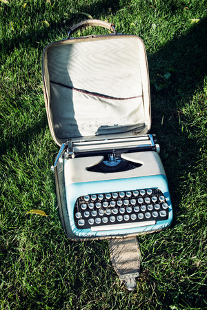 vertical composition: Old typewriter on the grass. Retro style. Vertical composition.