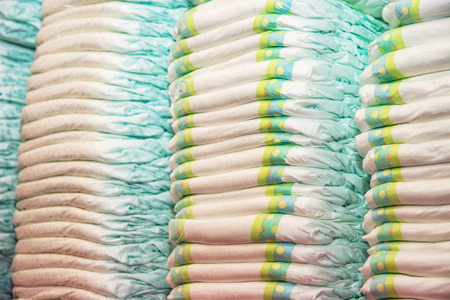 pampers: Childrens diapers stacked in a piles in the child room. Child hygiene.