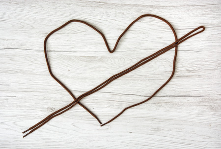heart shape: Brown shoelaces shaped in the heart on the wooden background. Valentines day. Symbol of lovers.