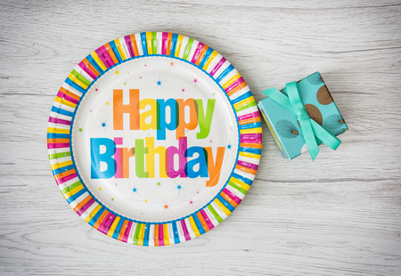 paper plates: Paper plates designed for birthday party with painted gift box on the wooden background. Holidays theme.