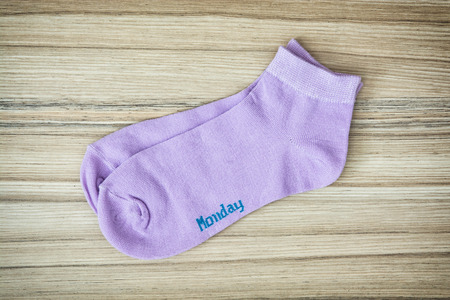 article of clothing: Trendy wool socks with inscription MONDAY on the wooden background.