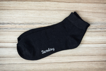 article of clothing: Trendy wool socks with inscription SUNDAY on the wooden background.