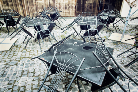 Set of metal garden chairs and tables in restaurant. It is closed. Outdoor street scene.