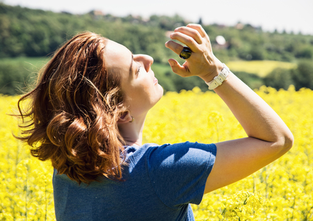 rappi: Young brunette woman in yellow rapeseed field. Sunlight. Rear view.
