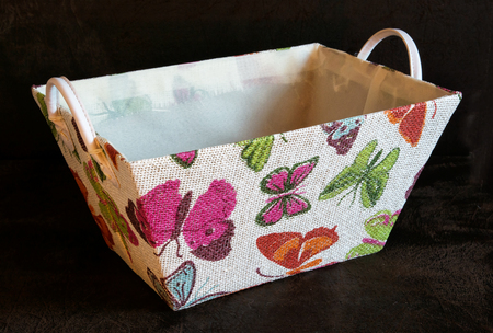 textil: Colorfull textil basket with butterflies on the dark background. Stock Photo
