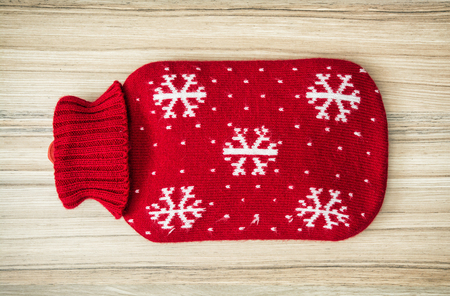 Red hot water bottle on the wooden background.