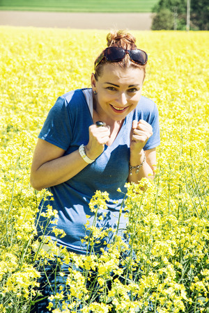 rappi: Young caucasian woman in the rapeseed field is afraid of insects. Beauty, fashion and nature. Stock Photo
