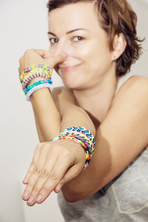 simulate: Young beautiful brunette with colorful rubber bracelets on her hands makes an elephant grimace.