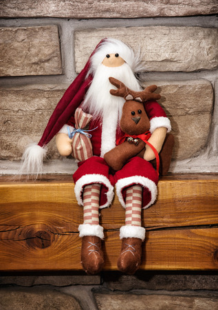 stone fireplace: Santa claus made of cloth is sitting with reindeer over the stone fireplace. Christmas decoration.