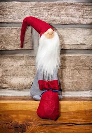 stone fireplace: Santa claus made of cloth with gifts is sitting over the stone fireplace. Christmas decoration.
