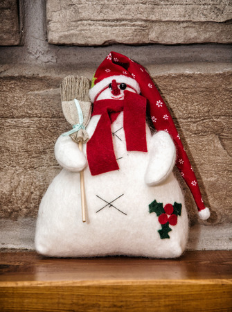 stone fireplace: White snowman with red hat and broom is sitting over the stone fireplace. Christmas decoration.