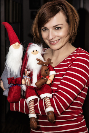 pleasure craft: Cheerful young caucasian woman posing with two cute santas. Christmas scene.