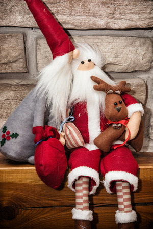 stone  fireplace: Two Santas made of cloth with reindeer sitting over the stone fireplace. Christmas decoration.