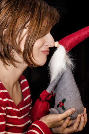 merry time: Cheerful young lady touches the nose with Santa Claus by Christmas time. Merry Christmas.