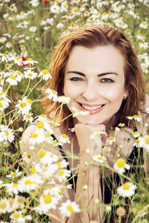 summer beauty: Young caucasian brunette woman posing in daisy meadow. Summer time. Beauty and nature.