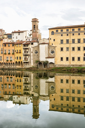 mirrored: Historical buildings with bell tower mirrored in the river Arno, Florence, Tuscany, Italy. Cultural heritage.