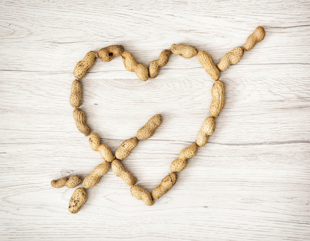 the human heart: Coraz�n de los cacahuetes en el fondo de madera. D�a de San Valent�n. S�mbolo de los amantes.