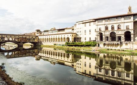 Beautiful Ponte Vecchio, Vasari Corridor and Uffizi Gallery are mirrored in the river Arno, Florence. Tuscany, Italy. Travel destination. Stock Photo