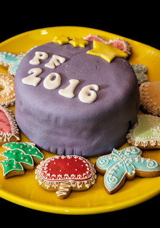 Detail of festive cake with the title PF 2016 and various gingerbread cookies on yellow plate.