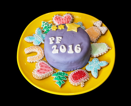 pour feliciter: The title PF 2016 written on festive cake with various gingerbread cookies on yellow plate.