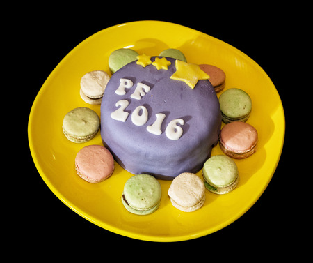 pour feliciter: The title PF 2016 written on festive cake with handmade macaroons on yellow plate.