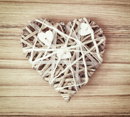 skillfully: Braided decorative valentine heart on the wooden background. Symbol of lovers.
