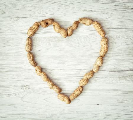 cacahuate: Hermoso corazón de los cacahuetes en el fondo de madera. Día de San Valentín. Símbolo de los amantes. Estilo retro.
