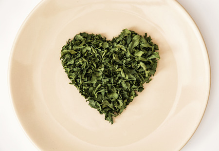 appetize: Heart shape of dried parsley on the plate. Valentines day. Symbol of lovers.