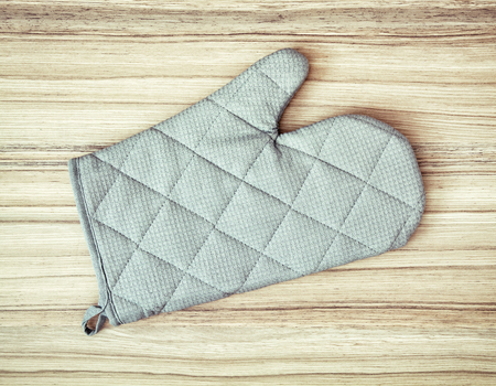 fireproof: Oven mitt (glove) or potholder on the wooden background.