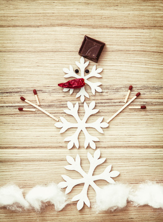 Beautiful snowman made of snow flakes, matches, chocolate and chili peppers on the wooden background. Symbol of winter.