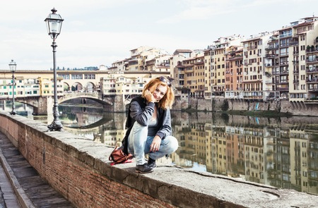 ponte vecchio: Beautiful young brunette woman posing in front of amazing bridge Ponte Vecchio, Florence, Tuscany, Italy. Travel destination. Stock Photo