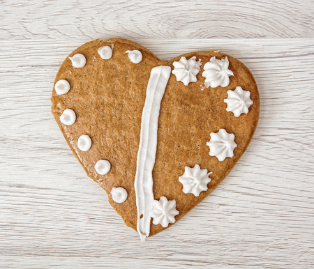 gingerbread heart: Tasty gingerbread heart of love on the wooden background. Valentines day. Symbolic shape.