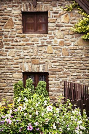 fiori di ibisco: Vecchia casa di mattoni, recinzione e ibisco legno fiori. Scena rurale. Archivio Fotografico