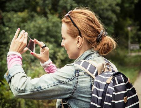 soltería: La mujer caucásica joven toma la foto con el teléfono inteligente en el parque.