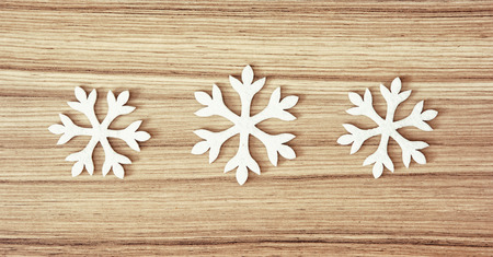 frost bound: Group of white snowflakes on the wooden background. Winter theme. Stock Photo