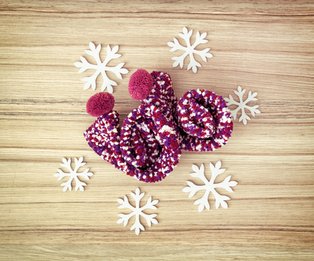 winter fashion: White snowflakes and colorful knitted socks on the wooden background. Winter fashion.