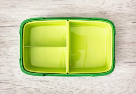 almuerzo: caja de plástico verde para el almacenamiento de alimentos en el fondo de madera. Foto de archivo