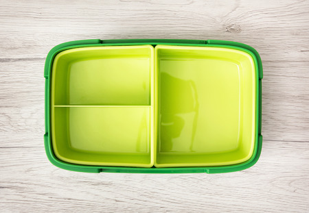 Green plastic box for food storage on the wooden background.