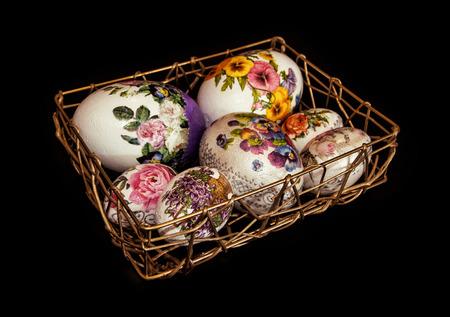 easteregg: Colorful Easter eggs stacked in golden wire basket. Easter holiday. Dark background. Symbol of springtime.
