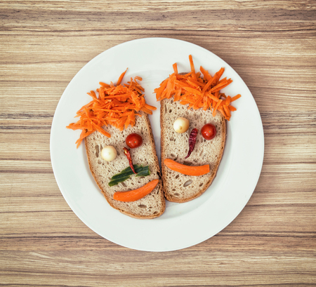 love shape: Vegetable faces made of bread, cheese, chilli, tomatoes and carrot. Couple in love. Valentines day.