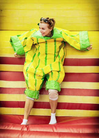 velcro: Joyful young woman in plastic dress in a bouncy castle imitates a fly on velcro wall. Inflatable attraction. Leisure activity.