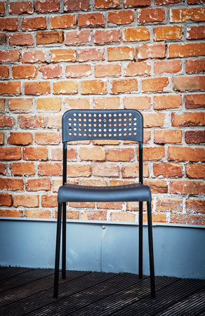 red chair: Metal chair in front of the brick wall. Modern living.