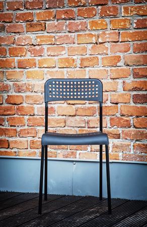 fondo rojo: silla de metal delante de la pared de ladrillo. Vida moderna. Foto de archivo