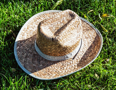 squatter: Farmers yellow straw hat in the grass. Rural symbol. Stock Photo