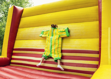 velcro: Young woman in plastic dress in a bouncy castle imitates a fly on velcro wall. Inflatable attraction. Leisure activity.