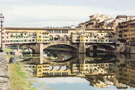 italian culture: Ponte Vecchio is mirrored in the river Arno, Florence, Tuscany, Italy. Travel destination. Cultural heritage. Italian culture.