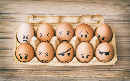 Emotion face painted eggs in paper box. Funny drawing faces. Stock Photo