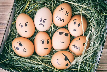 Emotion painted eggs in the box with hay. Funny drawing faces.
