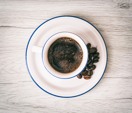 drink me: Ceramic cup of coffee with coffee beans on the wooden background. Pick-me-up. Morning ritual.